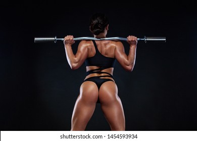 Strong muscular bodybuilder athletic woman pumping up muscles with barbell on black background. Workout bodybuilding concept. Copy space for sport nutrition ads and motivation text.