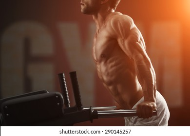 Strong muscular bodybuilder doing exercise on bars in the gym. Part of fitness body. Sports and fitness. Fitness man in the gym. Fitness training