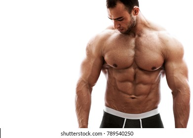 Strong muscular bodybuilder man with perfect trained body standing against white background and looking down. Place for text. High resolution