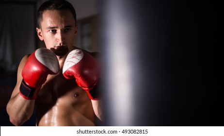 Strong muscular boxer in red boxing gloves.