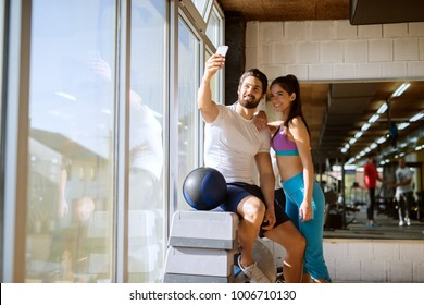 Strong muscular cheerful bearded man sitting in the corner of the gym on steppers and taking a selfie with his shape beautiful fitness girlfriend near the window.