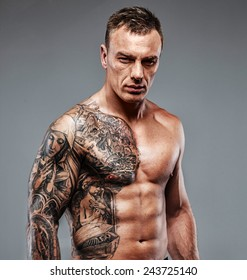 Strong muscular fighter with tattoo poses
