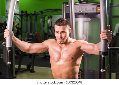 Strong muscular handsome man exercising at the gym