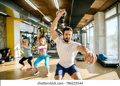 Strong muscular handsome young personal trainer doing exercises with kettlebells with two active sporty fitness women in the sunny modern gym.