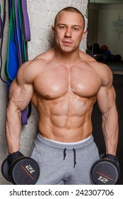 Strong muscular man bodybuilder shows his muscles holding dumbbells