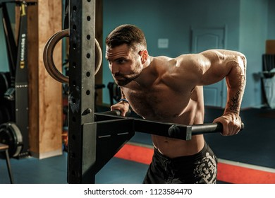 Strong muscular man doing push-ups on uneven bars in gym. Workout lifestyle concept.