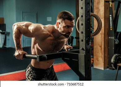 Strong muscular man doing push-ups on uneven bars in crossfit gym. Workout lifestyle concept.