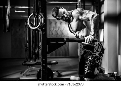 Strong muscular man doing push-ups on uneven bars in functional gym. Workout lifestyle concept.