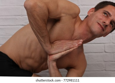 Strong muscular man doing yoga stretching exercises close up