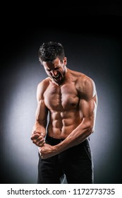 Strong muscular man feeling victory and enjoys success on dark background