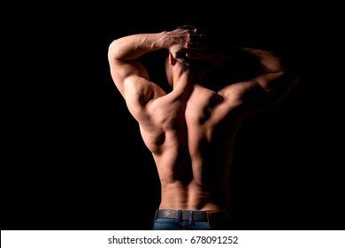 Strong muscular man holding his hands behind his head. Perfect shoulders and back muscles.
