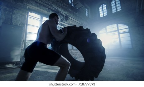 Strong Muscular Man Lifts Tire as Part of His Fitness Program. He's Covered in Sweat and Works out in a Abandoned Factory Remodeled into Gym.
