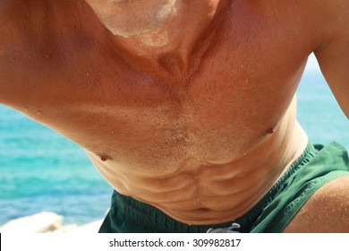 Strong muscular man on the beach, close on stomach and chest, six pack , abs. Sexy shirtless man enjoying sunny day on luxury water transport, active summer vacation