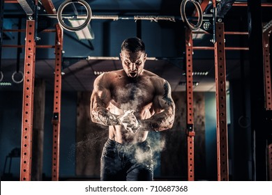 Strong muscular man preparing for workout in crossfit gym. Young athlete practicing cross-fit training