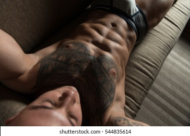 Strong Muscular Man in Underpants Sitting on a Couch