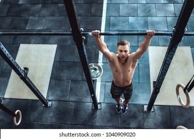 Strong muscular man is working out in gym. Cross fit training. Shirtless man doing pull ups.