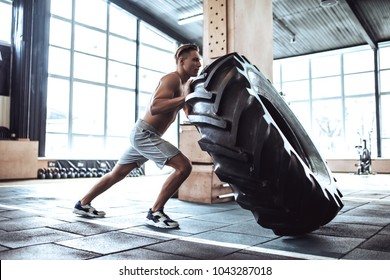 Strong muscular man is working out in gym. Cross fit training. Pushing tire.