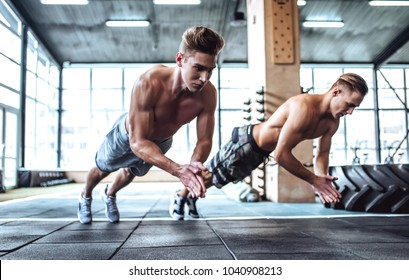Strong muscular men are working out in gym. Cross fit training. Making push-ups