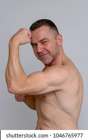 Strong muscular shirtless man showing off his biceps flexing his arm with a proud smile in a health and fitness concept over a light grey studio background
