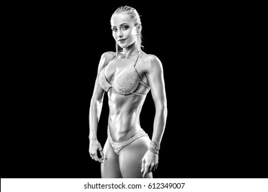 Strong and muscular sports girl in bikini standing and looking at the camera