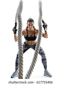 Strong muscular woman working out with ropes. Photo of attractive woman in sportswear isolated on white background. Strength and motivation.