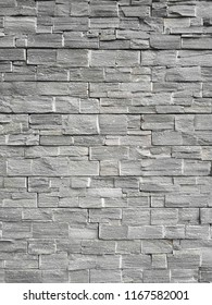 Strong natural gray brick stone wall background or texture. Pattern of black slate wall . Norway. Modern pattern of decorative slate stone wall Surface. Granite stone decorative brick wall seamless.