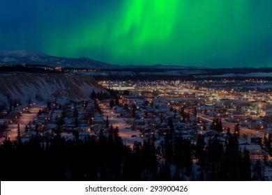 Fuerte subtormenta del norte (Aurora borealis) en el cielo nocturno sobre el centro de Whitehorse, capital del Territorio Yukón, Canadá, en invierno.