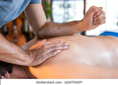 A strong physiotherapist hard massaging relaxed patient back side with his forearm. Physiotherapy, sports injury rehabilitation concepts