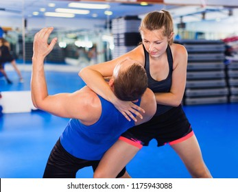 Strong positive   woman  is training captures with man on the self-defense course in gym.