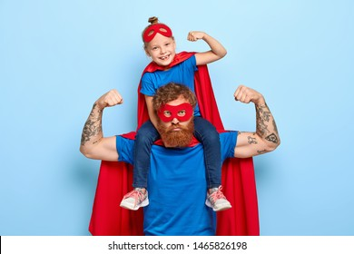 Strong powerful dad and little female child on his shoulders show muscles, ready to defend you and struggle, dressed in superhero clothes, isolated on blue background, prentend having superhuman power