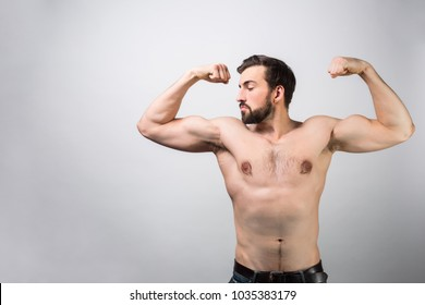 Strong and powerful guy without a shirt is standing at white wall and posing. He is showing his big muscles and how much strenght he has. He loves himself. Cut view. Isolated on white background.