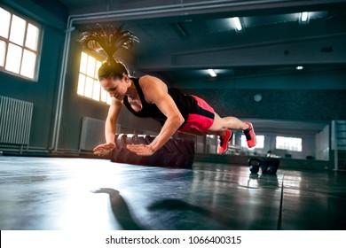 Strong powerful woman doing hard intense workout at gym, flying push ups