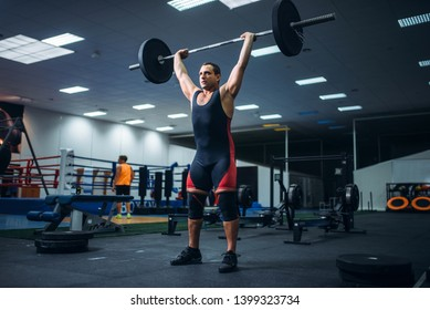 Strong powerlifter doing deadlift a barbell in gym