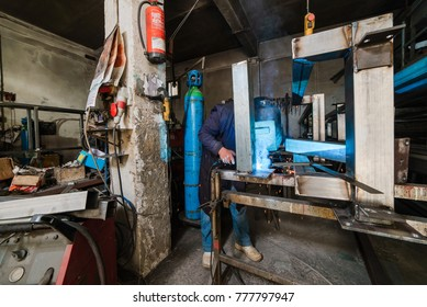Strong professional welder is welding a metal construction in garage wearing mask, proctive glasses and blue uniform. Blue sparks are flying apart.