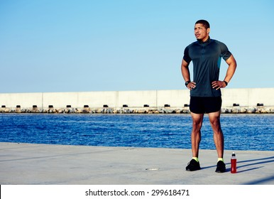 Strong pumped body man resting after workout in marina port while standing against the sea and sky background with copy space area for your text message or information, male jogger rest after running