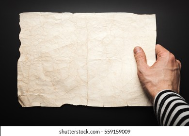 Strong sailor hand holds empty old crumpled paper sheet over black, pirate map copy-space background