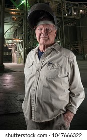Strong senior man with a welding helmet on standing in front of an industrial building at night with lights showing in the building