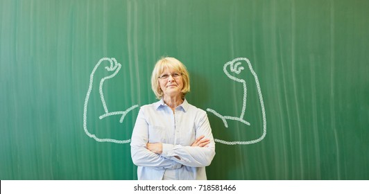 Strong senior teacher with chalk muscles in front of chalkboard