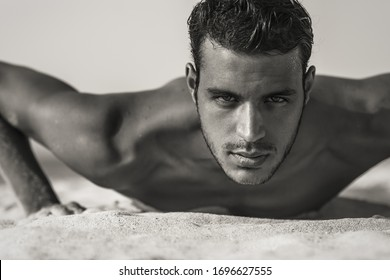 Strong sexy athletic male model portrait at the beach outdoors. Looking into camera.