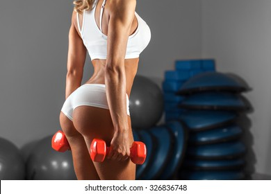 Strong sexy woman is training with dumbbells at the gym