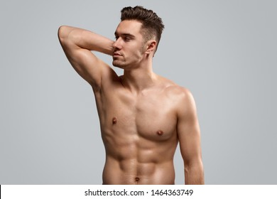Strong shirtless bodybuilder with hand behind head looking away against gray background