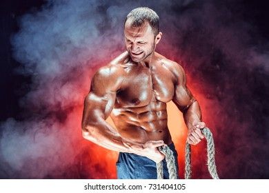 Strong shirtless bodybuilder man working out hard with rope.