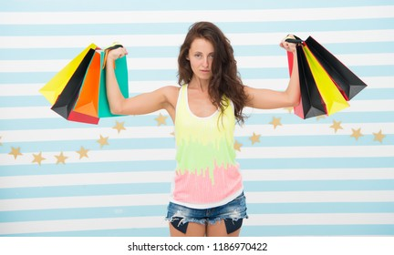 strong shopaholic girl hold shopping bags. beautiful shopaholic. girl holding colorful paper bags in strong hands. power of shopping therapy. this is perfect offer. woman with long hair hold purchase