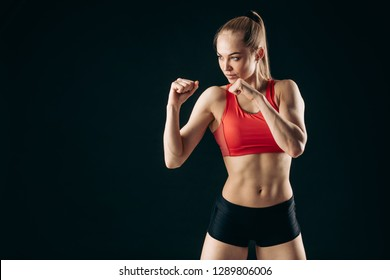 strong slim girl with ponytail is working out in boxing classes. close up photo.. isolated on the black background. poxing posture. position. competition