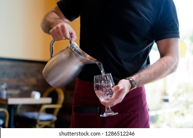 Strong slim man with muscular muscles working as a waiter in a restaurant in a black t-shirt and burgundy apron pours water from a stainless steel jug into a customers glass
