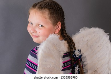 Strong smiling angel girl with wings.