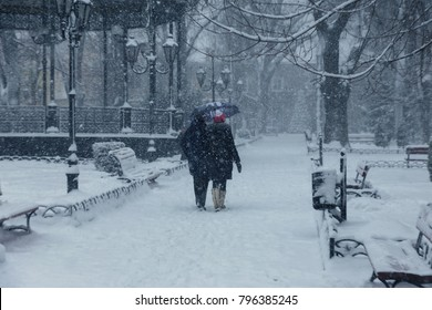 Strong snowfall in city streets in winter.  slippery road. Bad weather in winter: heavy snow and blizzard. Pedestrians go under heavy snow