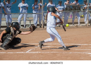 Strong softball player in black uniform expecting to catch the ball.