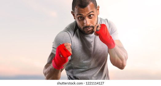 Strong sport man with boxing tapes fighting on sunset background