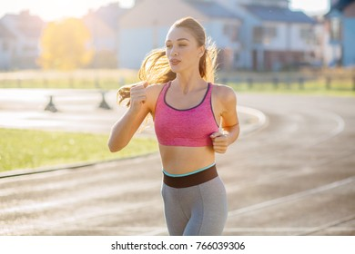 Strong sporty female runner with long hair in pink top and gray pants jogging outdoor on stadium track. Teenager healthy, sport and millennials people concept.
